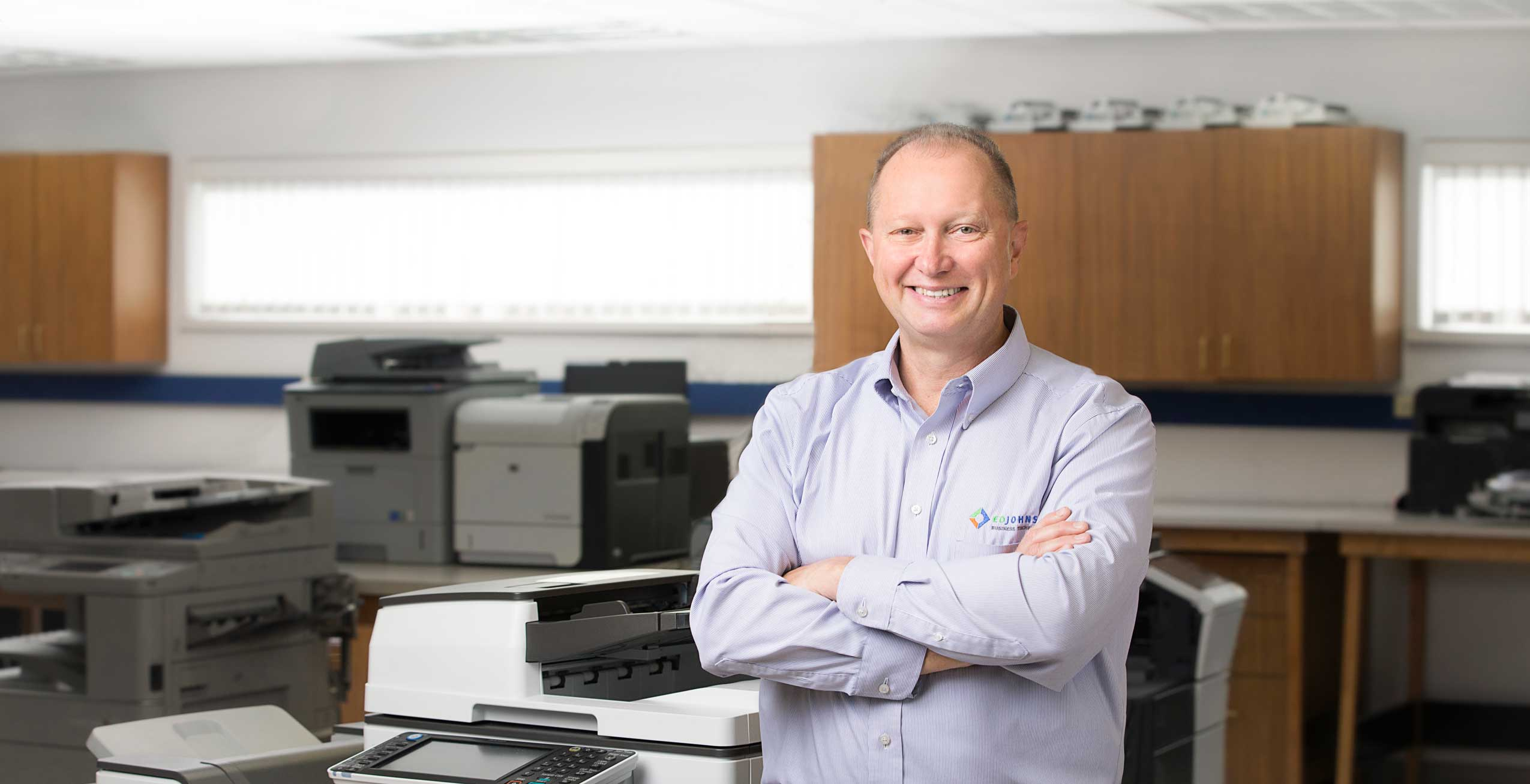 eo_johnson_employee_smiling_with_arms_crossed_next_to_copier