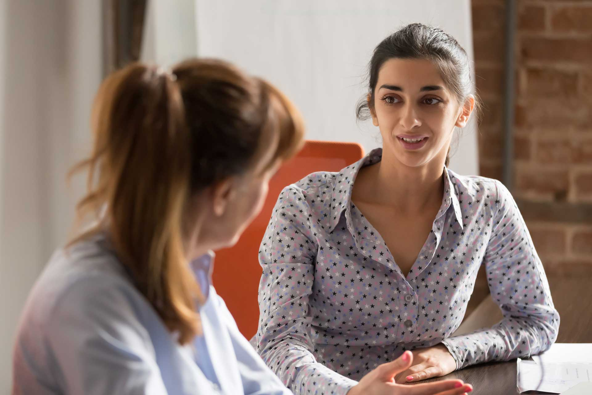 two_business_women_having_discussion_at_table