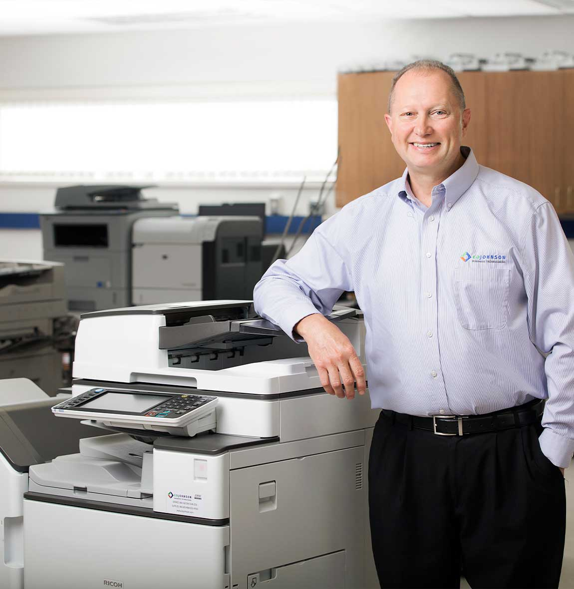 eo_johnson_employee_smiling_next_to_ricoh_copier